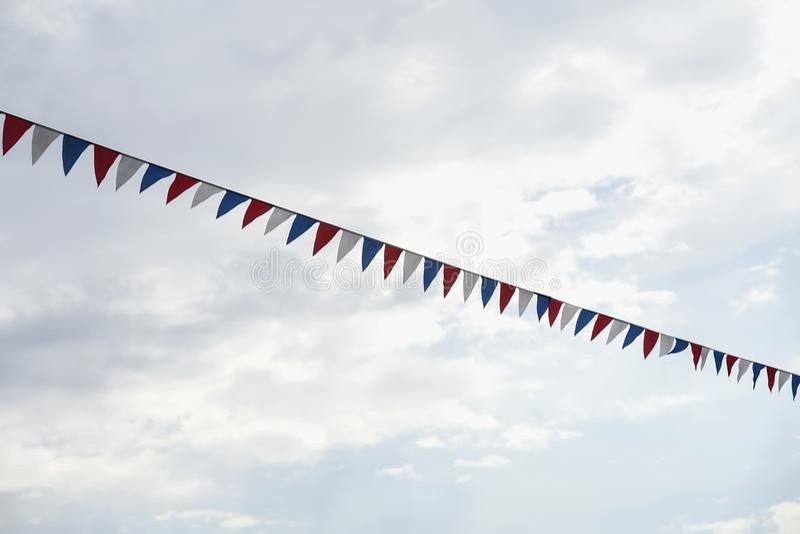 Nahaufnahmegirlande von multi farbigen Flaggen der dreieckigen Form, Wimpel im blauen Himmel Moderner Hintergrund, Fahnendesign stockbild