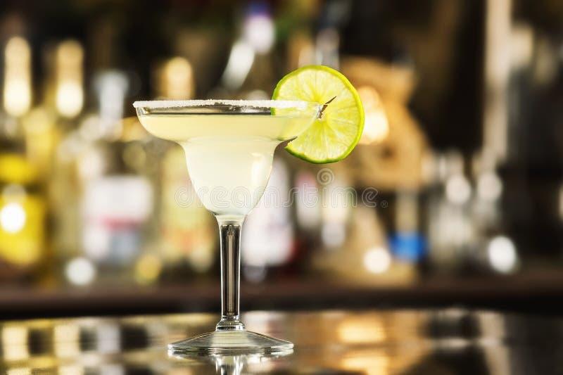 Nahaufnahmeglas des Margaritacocktails verziert mit Kalk an der Bar lizenzfreies stockbild