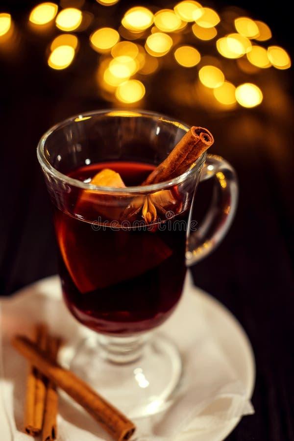 Nahaufnahmeglas Glühwein mit Orange und Zimt auf dunklem schwarzem Hintergrund, auf weißer Platte, Weihnachtslichter stockbilder