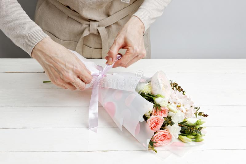 Nahaufnahmehände des Frauenfloristen verzieren einen Blumenstrauß von Blumen stockfotografie