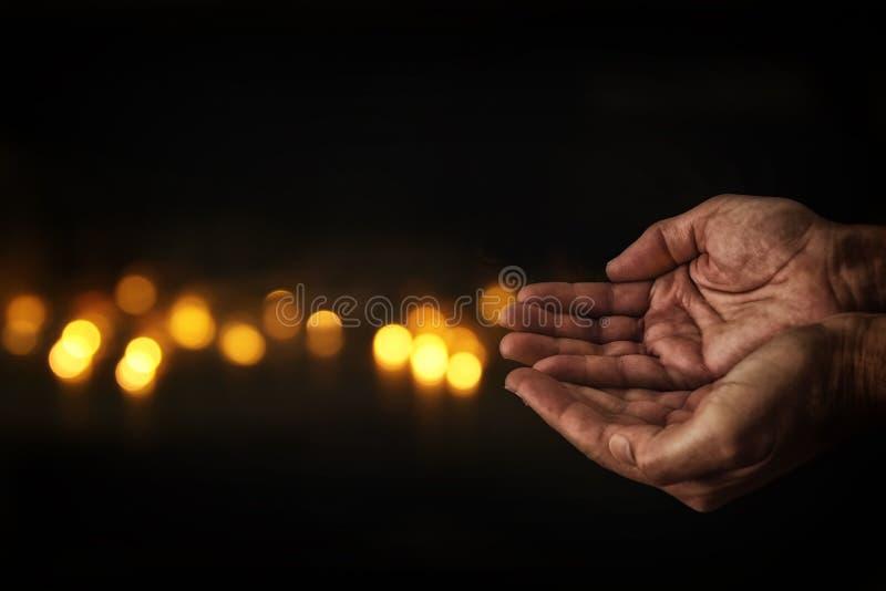 Nahaufnahmehände des Mannes bitten um Hilfe Konzept für Armut oder Hunger, suchend für Licht in der Dunkelheit lizenzfreie stockfotos
