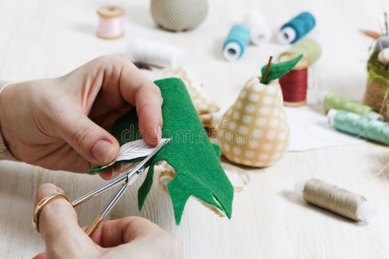 Nahaufnahmehände des Needlewoman halten Scheren und schneiden eine Torte heraus lizenzfreies stockfoto