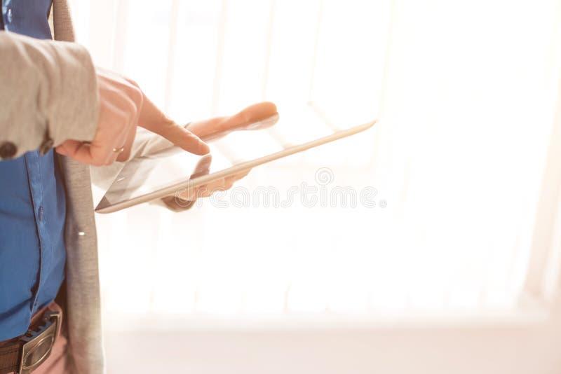 Nahaufnahmehände und Finger der Mannesrührenden digitalen Tablette über Fenster stockfotos