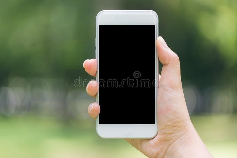 Nahaufnahmehand, die auf Lebensstilkonzept des mobilen leeren schwarzen Schirmes des Telefons im Freien auf undeutlichem Naturhin stockfotografie