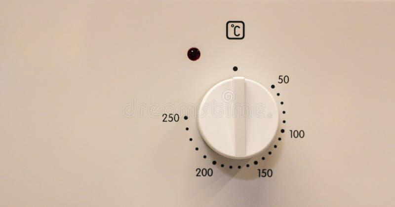Nahaufnahmehandeinstellung, die Modus oder Temperatur auf Ofen kocht lizenzfreie stockfotos