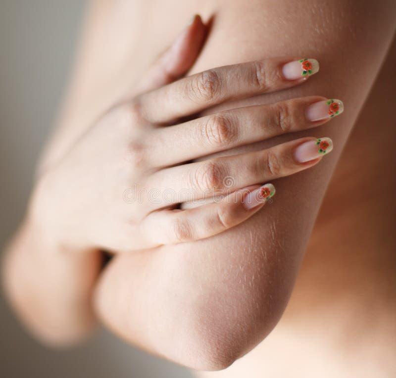 Nahaufnahmehandjunge Schönheitsnackte, die ihr Brust isola bedeckt lizenzfreie stockfotos