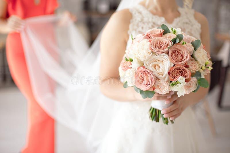 Nahaufnahmehochzeitsschuß des Kameraden den Brautschleier halten, der hinten von ihr auf unscharfem Hintergrund steht stockbilder