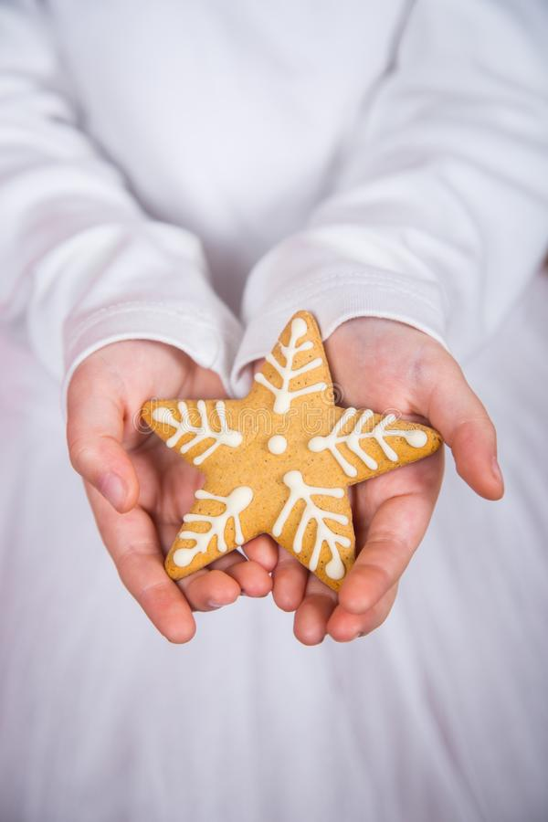 Nahaufnahmekind-` s übergibt das Halten des Weihnachtsplätzchens in der Form des Sternes stockfoto