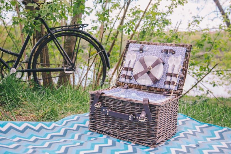 Nahaufnahmekoffer für Picknick mit Platten- und Esszimmergerätkosten auf blauer Abdeckung auf Gras auf Natur lizenzfreies stockfoto