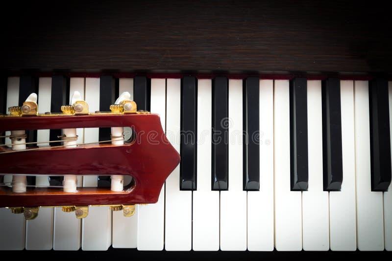 Nahaufnahmekopf der Gitarre auf Klaviertastatur stockfotografie