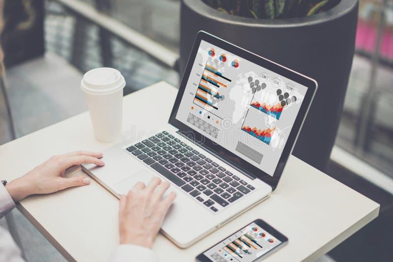 Nahaufnahmelaptop mit Diagrammen, Diagramme, Diagramme auf Schirm Auf Tabelle Tasse Kaffee und Smartphone lizenzfreie stockfotos