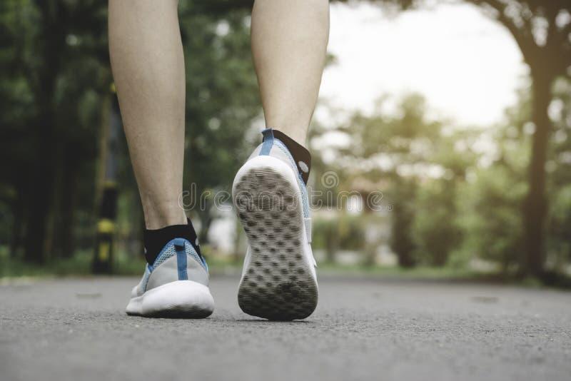 Nahaufnahmeleute, die mit Sportschuhen auf Stra?e im Park f?r Gesundheitskonzept gehen lizenzfreies stockbild