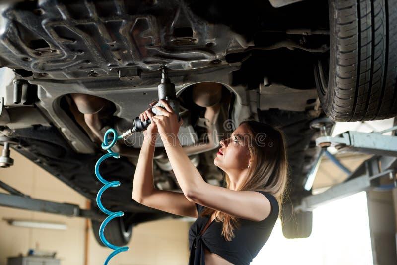 Nahaufnahmemädchen, das Auto mit pneumatischem Schlüssel auf Hebebühne repariert stockfotos