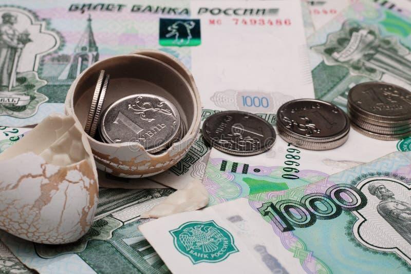 Nahaufnahmemünzen werden aus einer Eierschale heraus vor dem hintergrund der Papierrechnungen von tausend, viel russisches Geld g lizenzfreies stockfoto