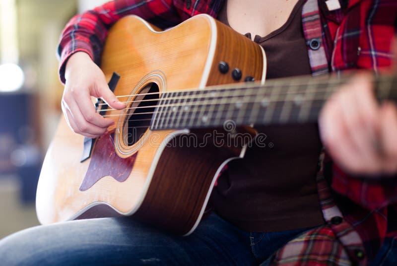 Nahaufnahmem?dchen spielt Akustikgitarre lizenzfreie stockfotos