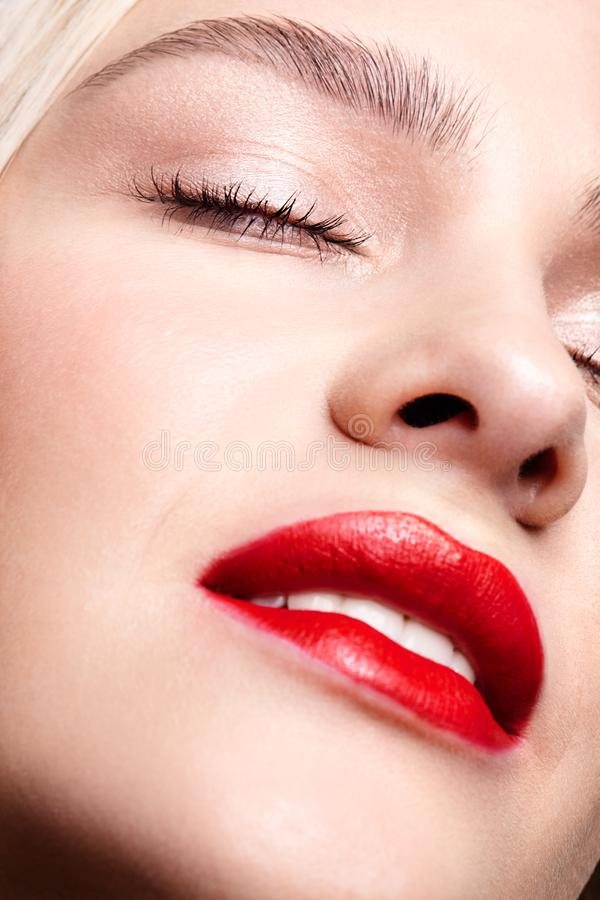 Nahaufnahmemakroporträt des weiblichen Gesichtes mit den roten lächelnden Lippen und Schönheitsmake-up lizenzfreie stockbilder