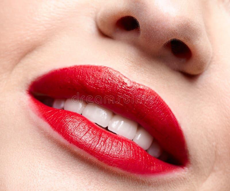 Nahaufnahmemakroporträt von weiblichen roten lächelnden Lippen mit Tagesschönheitsmake-up lizenzfreie stockbilder
