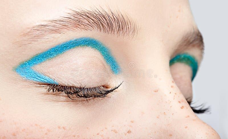 Nahaufnahmemakroschuß des geschlossenen menschlichen weiblichen Auges und mit blauem rauchigem Augenschatten stockfotos