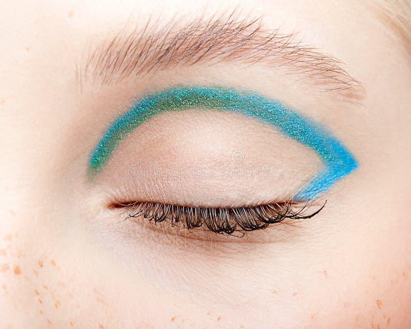 Nahaufnahmemakroschuß des geschlossenen menschlichen weiblichen Auges und mit blauem rauchigem Augenschatten lizenzfreie stockfotos