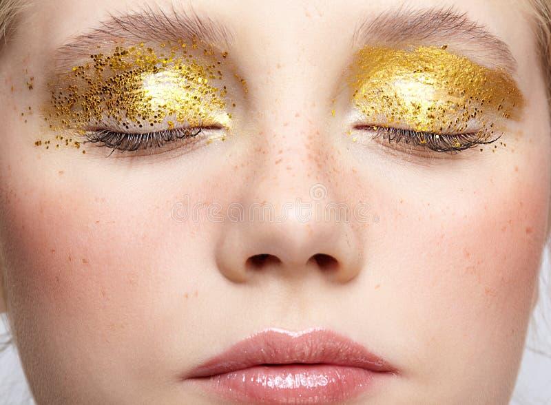 Nahaufnahmemakroschuß des geschlossenen menschlichen weiblichen Gesichtes mit gelbem rauchigem Augenschönheitsmake-up stockbild