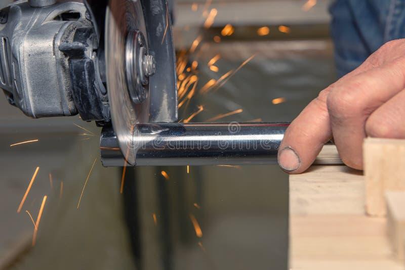 Nahaufnahmemann arbeitet mit Handbatterierundschreiben sah geschnittenes Metall stockfotos