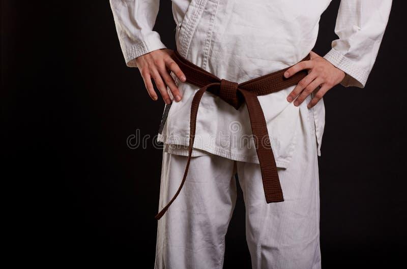Nahaufnahmemann im weißen Kimono mit braunem Gurt auf einem schwarzen Hintergrund Getrennt auf Weiß stockbild