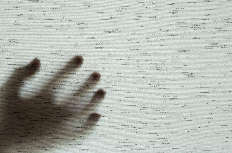 Nahaufnahmeoberflächenschatten der Hand hinter grauem Gewebevorhang maserte Hintergrund mit Kopienraum im Horrorkonzept stockbilder