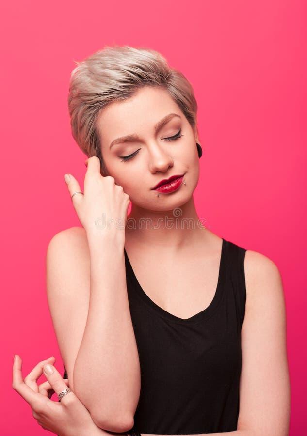 Nahaufnahmeporträt blonden Frau der Junge der recht auf rosa Hintergrund stockfoto