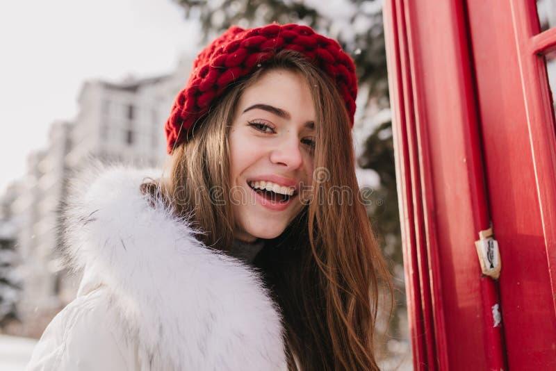 Nahaufnahmeporträt, das nette junge Frau mit dem langen brunette Haar, im roten Hut, positive Gefühle zur Kamera an ausdrückend ü stockbild