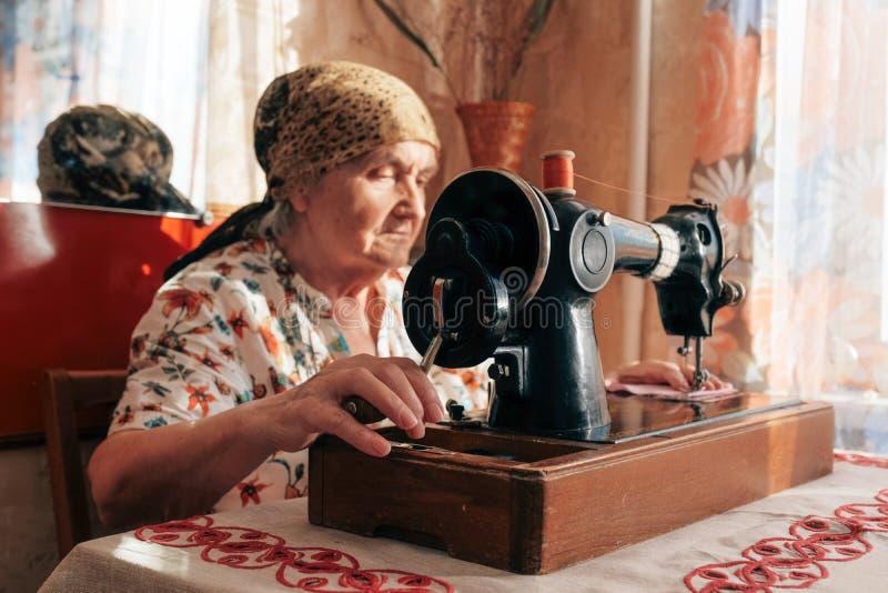 Nahaufnahmeporträt der alten Frau unter Verwendung der Nähmaschine, 70 Jahre Näherin, die zu Hause arbeiten stockfoto