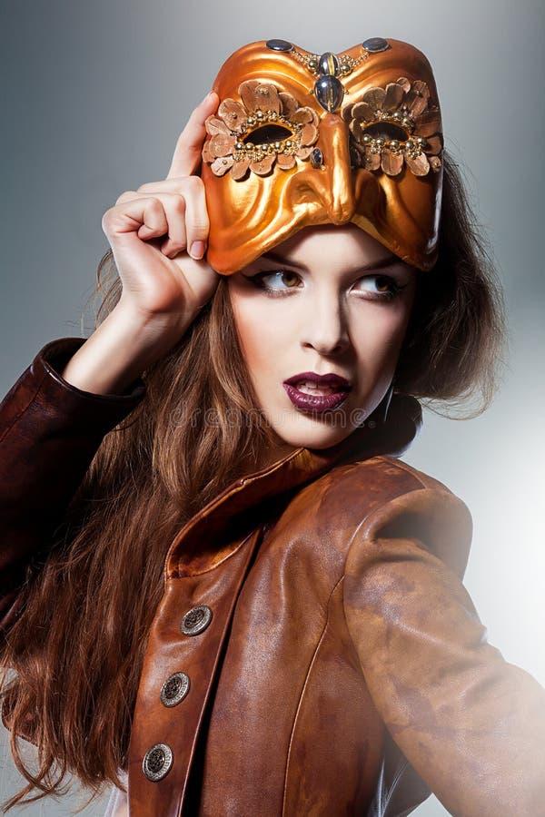 Nahaufnahmeporträt der attraktiven Frau in der Maske und in der Jacke stockfotografie