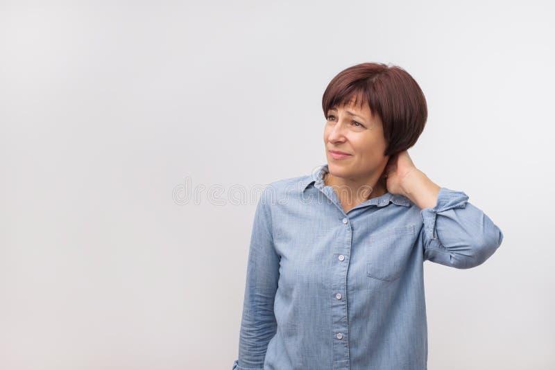 Nahaufnahmeporträt der besorgten reifen schönen Frau, die auf grauem Wandhintergrund mit Kopienraum steht stockfotos