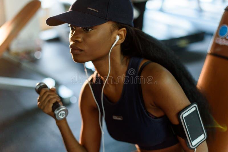 Nahaufnahmeporträt der Eignungslehrer-Afroamerikanerfrau, die mit Dummköpfen an der Turnhalle ausarbeitet und hört Musik stockfotografie