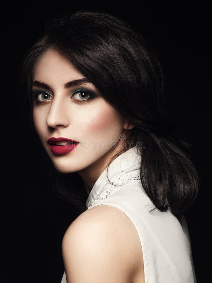 Nahaufnahmeporträt der eleganten jungen Frau über dunklem Hintergrund lizenzfreie stockfotos