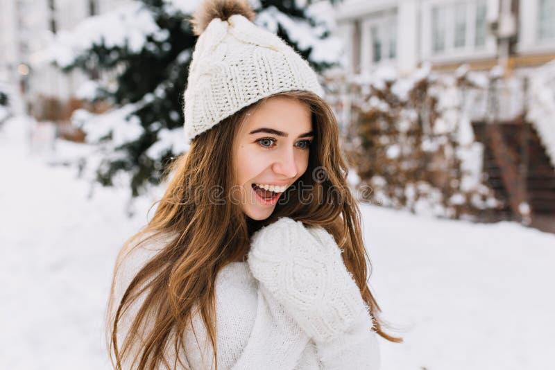 Nahaufnahmeporträt der erstaunten frohen jungen Frau, die Spaß auf Straße, gefrorenes Wetter des Winters hat Langes brunette Haar lizenzfreie stockfotografie