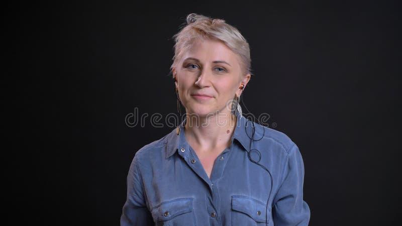 Nahaufnahmeporträt der erwachsenen attraktiven kaukasischen Frau in den Schwingungen hörend Musik und mit der Freude lächelnd, di lizenzfreie stockfotografie