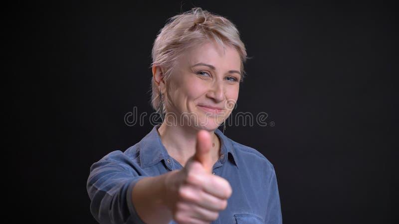 Nahaufnahmeporträt der erwachsenen attraktiven kaukasischen Frau, die nett lächelt und oben Daumen beim Betrachten der Kamera ges stockfoto
