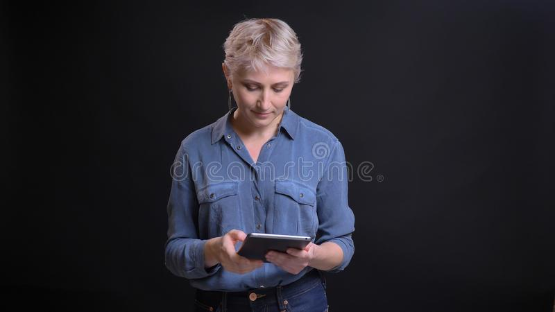 Nahaufnahmeporträt der erwachsenen hübschen kaukasischen Frau mit dem kurzen blonden Haar unter Verwendung der Tablette vor der K stockfoto