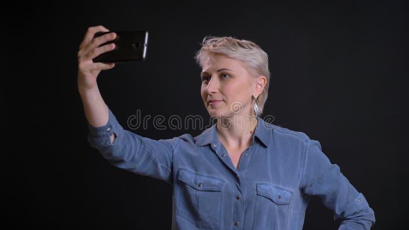 Nahaufnahmeporträt der erwachsenen kaukasischen Frau mit dem kurzen blonden Haar, das selfies am Telefon mit dem Hintergrund loka lizenzfreie stockfotos