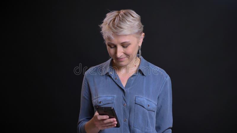 Nahaufnahmeporträt der erwachsenen kaukasischen Frau mit dem kurzen blonden Haar, das am Telefon vor der Kamera simst lizenzfreie stockfotografie