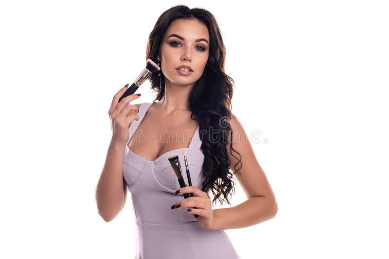 Nahaufnahmeporträt der Frau mit Make-upbürste nahe Gesicht stockfotografie