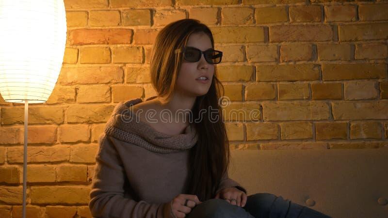 Nahaufnahmeporträt der jungen attraktiven kaukasischen Frau, die im Fernsehen einen Film in den Gläsern 3D mit aufgeregter Gesich stockfotografie