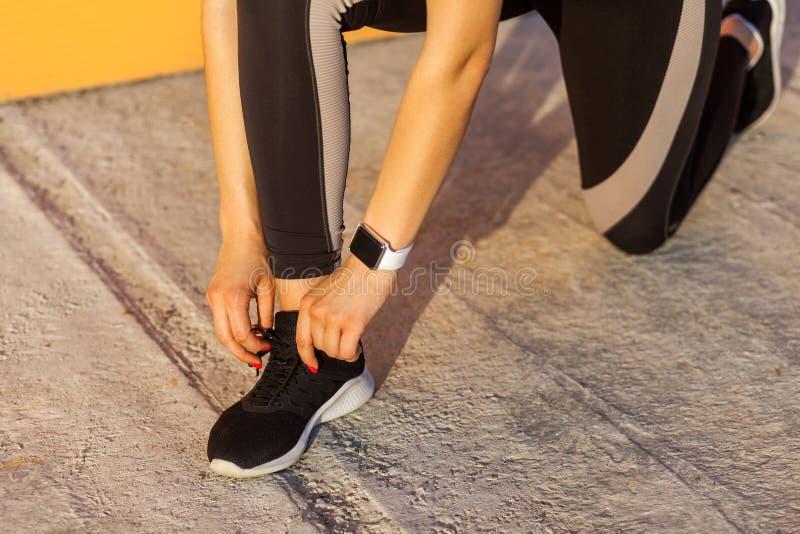 Nahaufnahmeporträt der jungen attraktiven sportlichen Frau, die schwarzes sporwear am Morgen auf Straßenstellung auf Knie trägt u lizenzfreie stockbilder