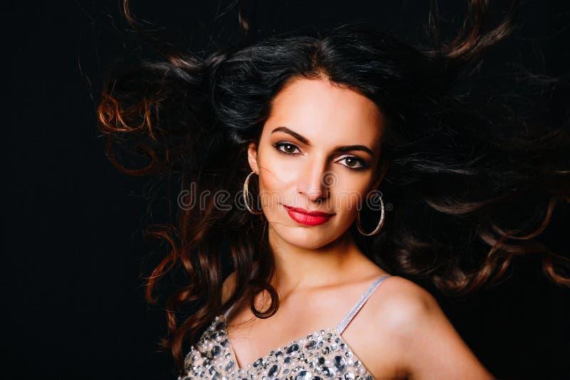 Nahaufnahmeporträt der jungen Brunettefrau mit dem langen gelockten Haar, das auf einem dunklen Hintergrund aufwirft, und Blicke  stockfotografie