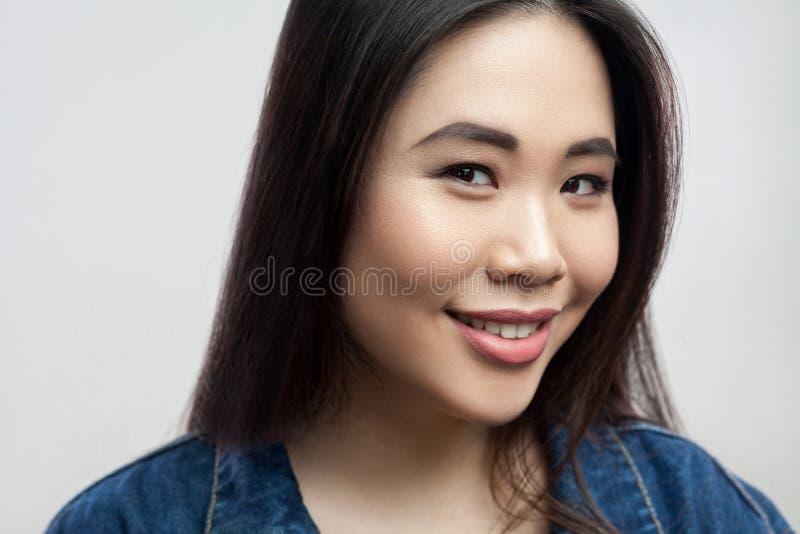 Nahaufnahmeporträt der jungen Frau des frohen schönen brunette Asiaten mit Make-up und gerader Stellung des dunklen Haares und de stockbild