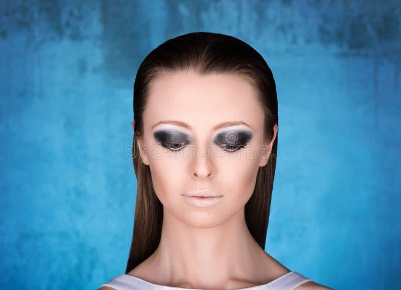 Nahaufnahmeporträt der jungen Frau mit Berufsmake-up Modell schaut unten stockfotografie