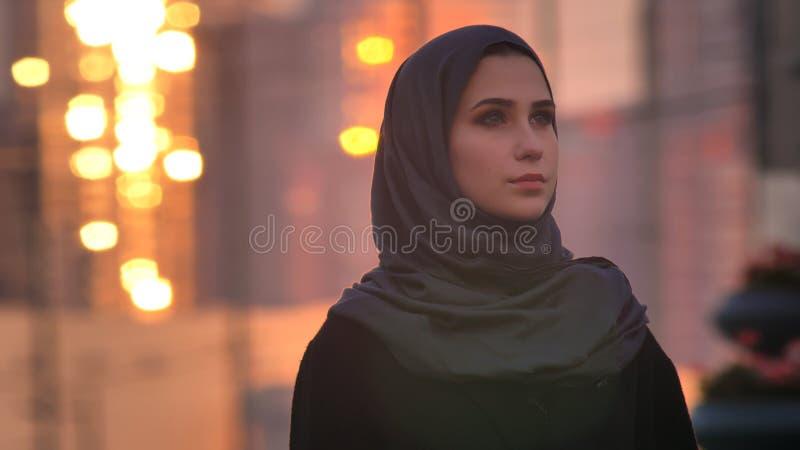 Nahaufnahmeporträt der jungen hübschen Frau im hijab, das mit städtischer Stadt und glänzenden Gebäuden auf direkt schaut lizenzfreies stockbild