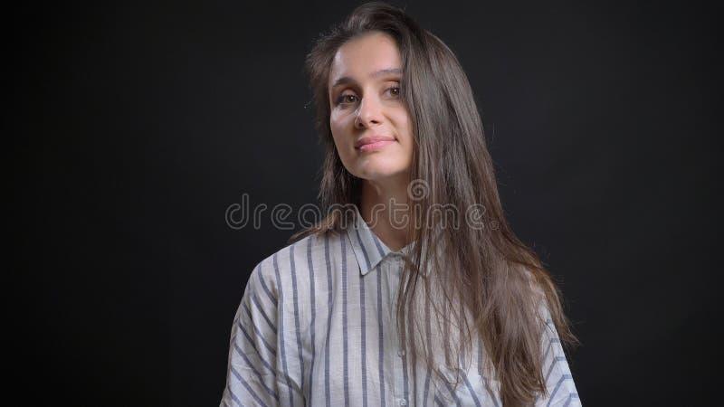 Nahaufnahmeporträt der jungen hübschen kaukasischen Frau mit dem brunette Haar, das Kamera betrachtet und verlockend mit lächelt lizenzfreie stockbilder