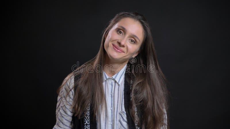Nahaufnahmeporträt der jungen hübschen kaukasischen Frau, welche die Kamera lächelt und lehnt ihren Kopf zur Seite betrachtet lizenzfreies stockfoto