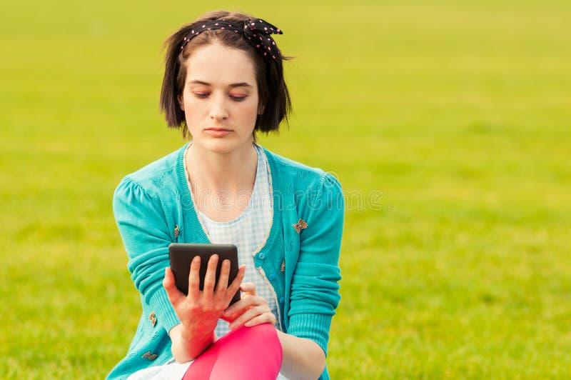 Nahaufnahmeporträt der jungen Hippie-Frau mit Tablette im Park stockfotografie